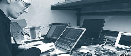 Chaos - Wie früher gearbeitet werden musste. Ein Student sitzt vor drei einzelnen Computern.