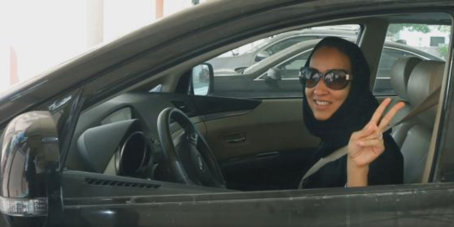 A woman with a headscarf and dark sunglasses showing the peace sign is sitting in a car.